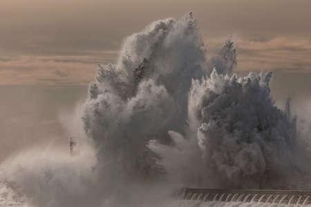 Big wave splash. Douro river mouth north pier and beacon. Archivio Fotografico