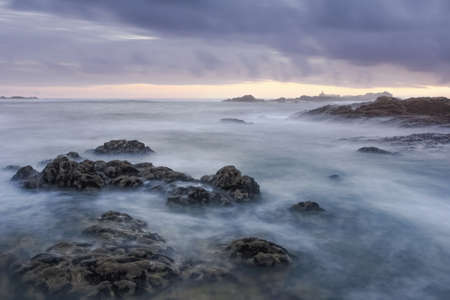Last rays of light on a romantic rocky beach in the north of Portugal during low tide.