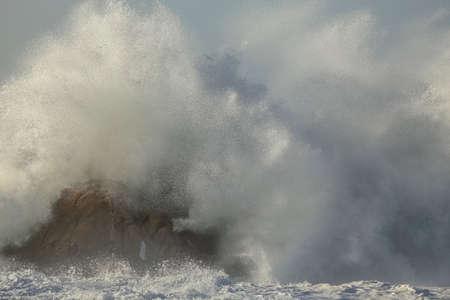Big wave splash in a stormy but sunny day. Nortern portuguese rocky coast. Archivio Fotografico