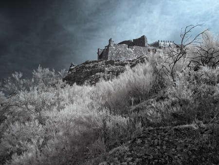 Infrared european medieval castle on the peak of a mountain Archivio Fotografico