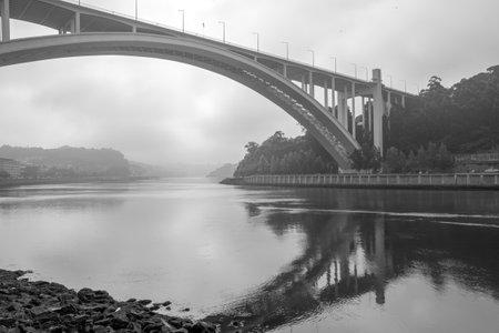 Arrabida bridge, Douro river, Porto, Portugal, in a misty and cloudy morning.