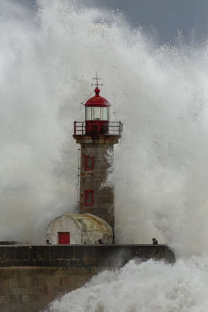 Porto, Portugal - February 7, 2016: Big ocean waves against old lighthouse and pier in a stormy afternoon seeing people fleeing. Archivio Fotografico