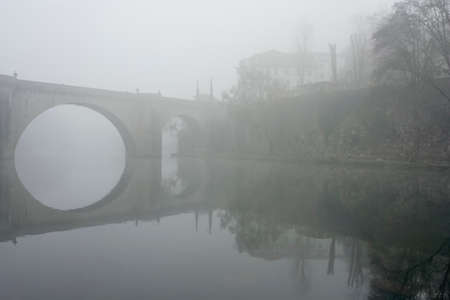 Romantic old river bridge in the middle of fog. Tamega bridge, Amarante, north of Portugal.