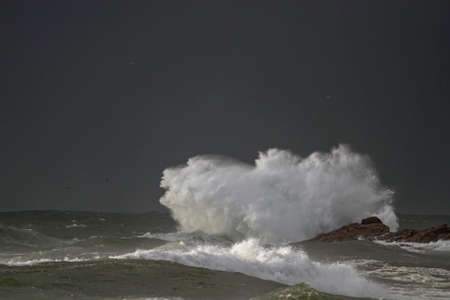 Storm on the coast seeig big wave breaking over rocks and cliffs seeing splash and spray
