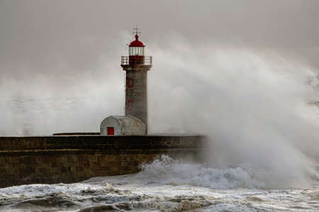 Douro river mouth new north pier and beacon under heavy storm seeing spray from the big breaking waves.