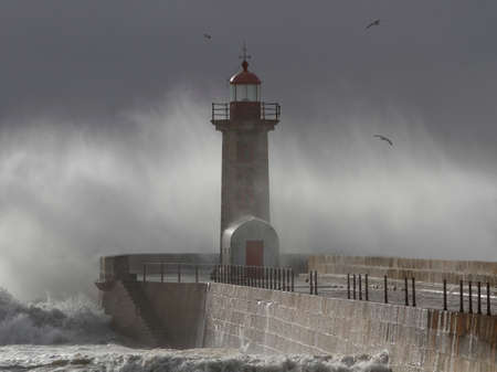 Douro river mouth old north pier and beacon under heavy storm seeing spray from the big breaking waves. Archivio Fotografico