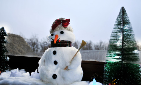 serbia xmas: White smiling snowman stands still past in front of a cold window on a cold winter day in the heat of the house in a small village near Novi Sad, Serbia