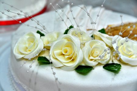 Cute delicious wedding cake decorated with cakes in the shape of red and white roses on the sides decorated with various beads and lines
