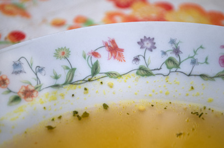 Domestic soup with noodles in a plate decorated with flowers Stock Photo