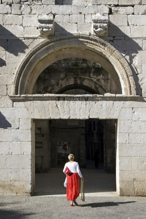Woman in red skirt entered to Diocletian palace through the Golden gate Фото со стока