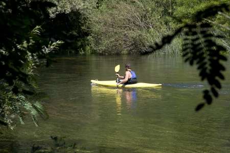 Young adult man kayaking down the river Cetina in Croatia photo