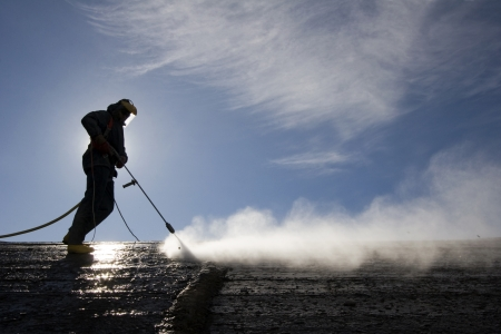 Worker on top of factory hall, with high pressure washer, cleans layer of old concrete photo
