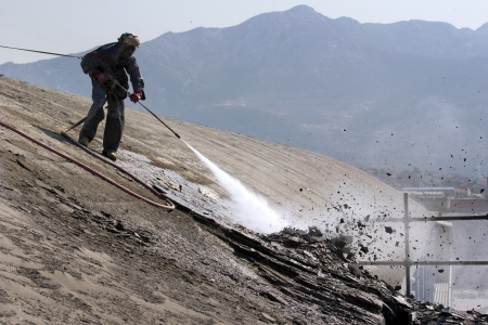 Worker on top of factory hall, with high pressure washer, cleans layer of old concrete