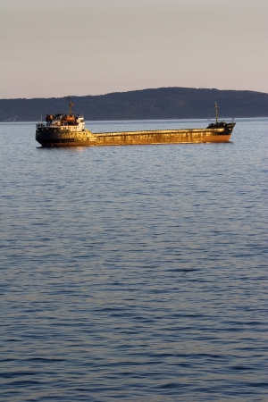 seaway: Rusty cargo ship anchored in front the Brac island, Croatia
