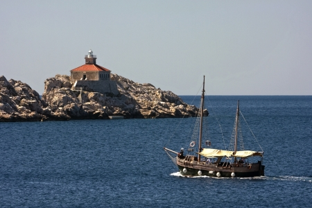 sureness: Lighthouse on the rock near Dubrovnik and old wooden boat