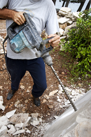Man drills holes with drilling machine in stone block