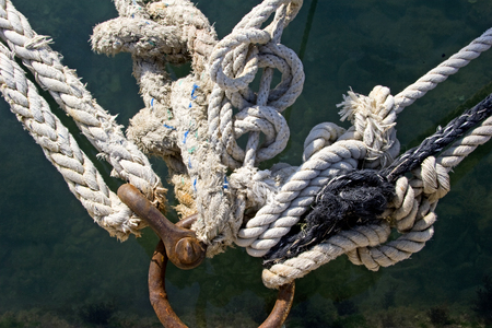 Rusted mooring ring with naval ropes on the pier Stock Photo