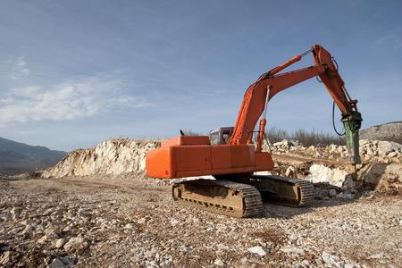 Orange backhoe drilling stone soil on construction of road Stock Photo
