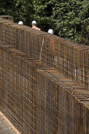 Construction workers between steel bars, iron armature on construction site of new railway bridge Фото со стока