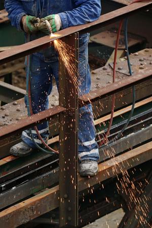 Welder using cutting torch to cut an old iron bridge fence Фото со стока