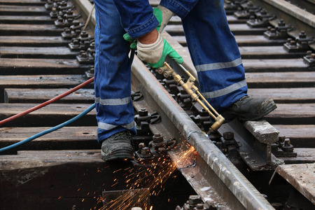Welder cut a rail using cutting torch Stock Photo