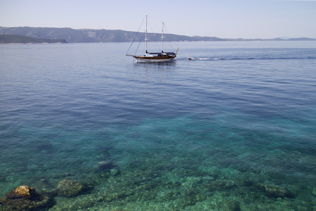 Wooden sailing boat with two masts near coastline of Brac island