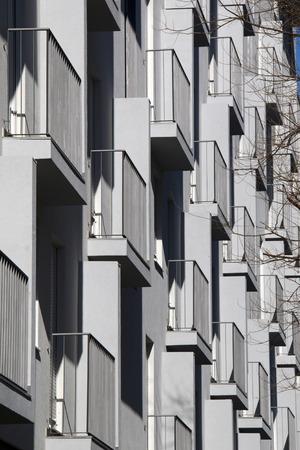 Balconies on gray building facade with metal fences Фото со стока
