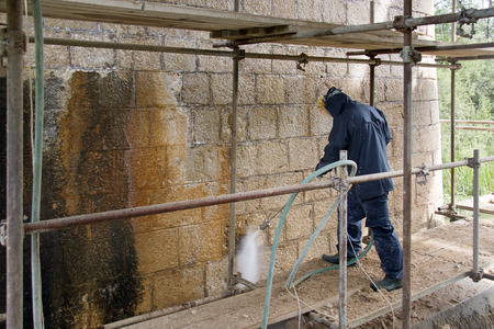 Construction worker cleaning dirtiness with high pressure washer from ancient stone wall Фото со стока