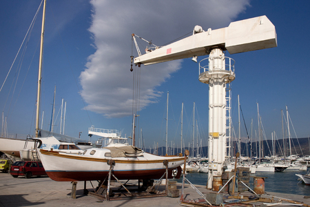 White crane for lifting boats in marina