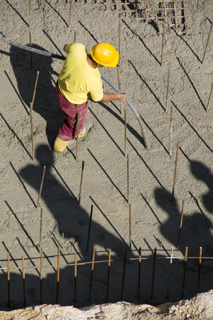 Construction worker vibrating concrete foundations of hydro power plant