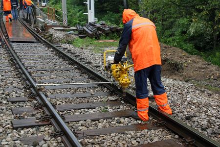 Worker repairs railroad on rainy day with machine Фото со стока