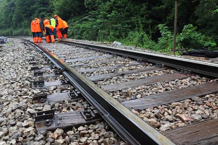 Workers in orange  raincoats repair railroad on rainy day