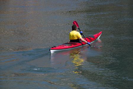 Man in yellow t shirt kayaking on the river Cetina near town Omis in Croatia