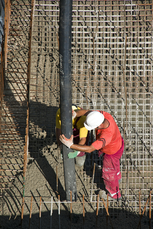 Two construction workers casting foundations of hydro power plant