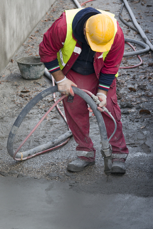 Construction worker casting concrete with pump Stock Photo