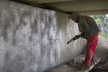 Worker renews concrete viaduct with sprayed concrete