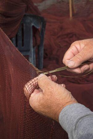 Needle with thread in fisherman hands repairing net for catching sardine