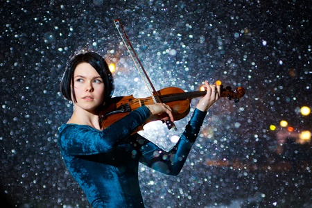 Girl in green dress with violin on snow photo