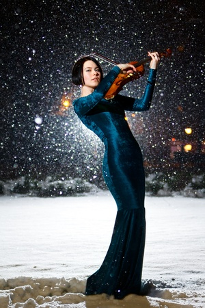 Girl in green dress with violin on snow