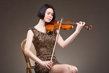 Mädchen mit Geige in goldenem Kleid Standard-Bild