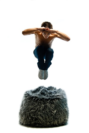 beanbag: Young man jump over bean-bag isolated on white