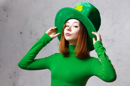 Red hair girl in Saint Patrick s day hat isolated on grey grunge background Imagens