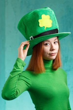 緑のグランジ背景に分離された聖者の Patrick s の日帽子の赤い髪の少女