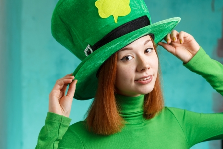 Red hair girl in Saint Patrick s day hat isolated on green grunge background 免版税图像