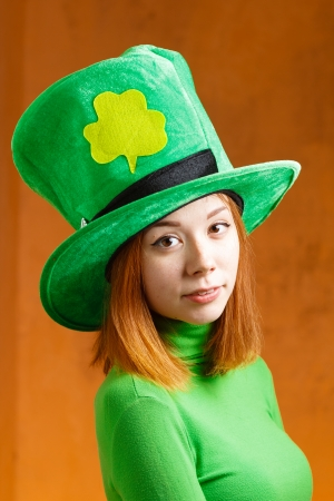 Red hair girl in Saint Patrick s day hat isolated on orange grunge background photo