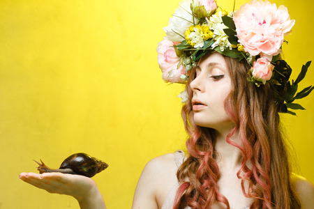 calm pretty girl with snail in hand and flower crown on head on yellow background Imagens