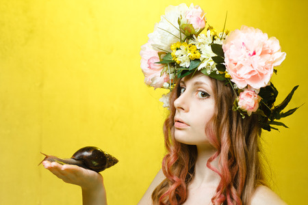 sexy girl posing: calm pretty girl with snail in hand and flower crown on head on yellow background Stock Photo