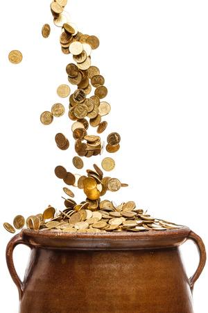 cash money: las monedas de oro que cae en el crisol de la vendimia aislado en el fondo blanco Foto de archivo