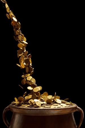 黒い背景に分離されたビンテージ ポットに落ちる金の硬貨