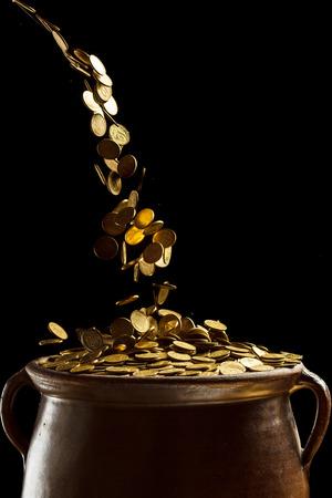 Gold-Münzen fallen in der Vintage-Topf isoliert auf schwarzem Hintergrund Standard-Bild